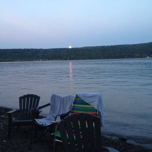 The full orange moon begins to rise over the Bluff and reflect upon the water.  Abandoned chairs hold wet towels.