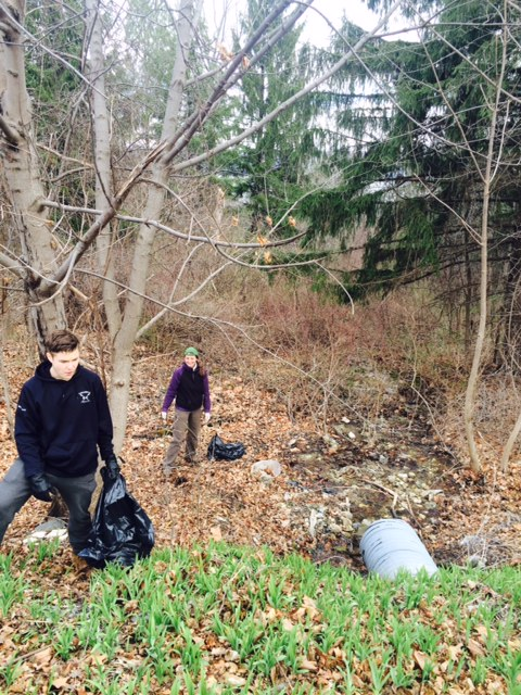 Volunteers work together to clear this stream of trash
